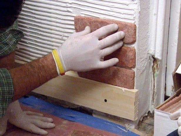 Монтаж декоративного камня. Первый ряд подпирается деревянным или металлическим профилем
