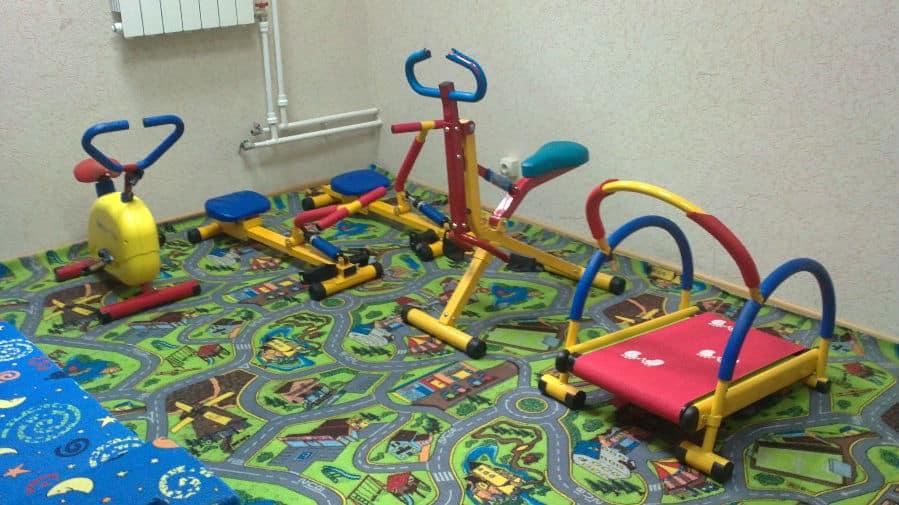 Для детей можно выделить отдельную зону спортзала. Желательно, чтобы она находилась максимально далеко от тяжелых взрослых спортивных тренажеров и снарядов